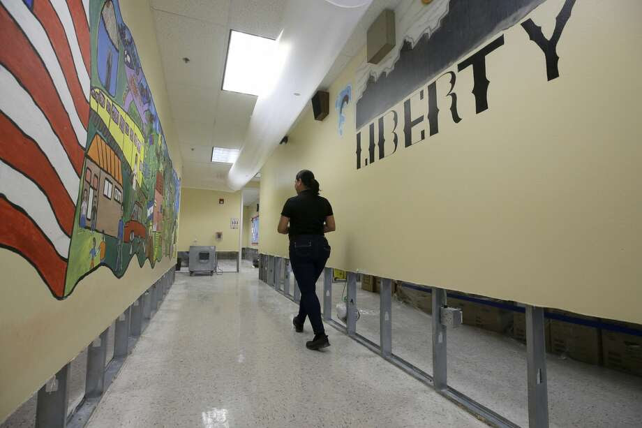 Mary Pinales, with Blackmon Mooring, walks through Liberty High School, 6400 Southwest Fwy., where the walls were cut two feet up to dry out the school Thursday, Aug. 31, 2017, in Houston.  Many schools were damaged from flooding in the aftermath of Hurrican Harvey. ( Melissa Phillip / Houston Chronicle ) Photo: Melissa Phillip/Houston Chronicle