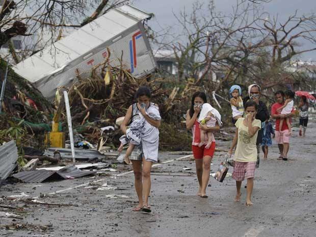 Sobreviventes tampam o nariz debido ao odor de corpos em estado avançado de decomposição espalhados por Tacloban. Supertufão pode ter matado 10 mil pessoas no país, estimam autoridades. (Foto: Bullit Marquez / AP Photo)