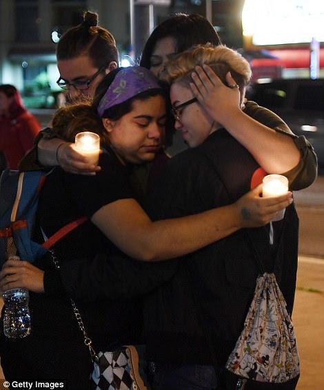 Gabby Phillips, Sam Alworth, Ana Preciado and Evan Dixon embrace during a vigil on the Las Vegas strip