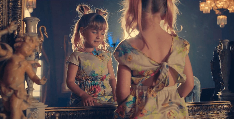 The young girl follows a blue Monarch butterfly through a mirror.