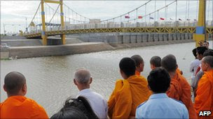 Cambodian Buddhist monks and other mourners look at Diamond Gate bridge