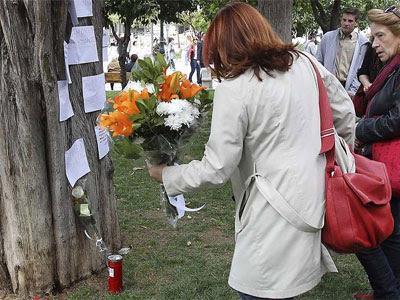 Una mujer deposita flores en el lugar donde el jubilado griego Dimitris Christoulas se suicidó en abril. EFE
