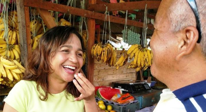 Eliziane experimenta fruta e conversa com barraqueiro da feira da Cidade Operária