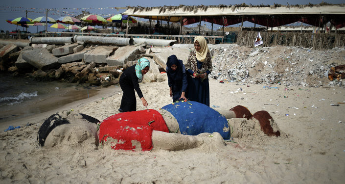 Palestinian girls put flowers on a sand sculpture depicting Syrian boy Aylan Kurdi, a three-year-old boy who drowned off Turkey, on September 7, 2015, on Gaza city beach
