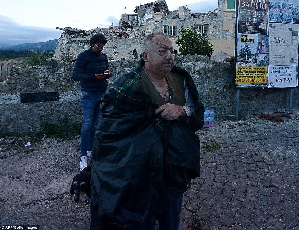 Envolta em cobertores, um homem gravemente ferido olha para sua cidade natal destruída de Amatrice que foi cortado do mundo depois de suas estradas foram enterrados em escombros