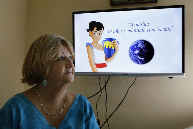 Angela Corvea sits in front of the image of Acualina, the educational project she created 15 years ago in Cuba to teach children - and their families - how to reduce environmental risks, including climate risks, in an island nation where the impacts of rising temperatures are very noticeable. Credit: Jorge Luis Baños/IPS