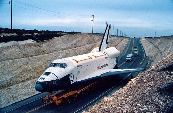 Space shuttle Enterprise is driven through rocky terrain at Vandenberg AFB in California.