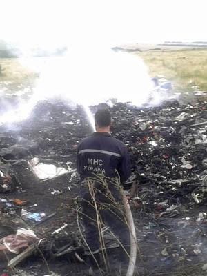 Homem apaga incêndio no local da queda do avião Malaysia Airlines Boeing 777 na região de Donetsk (Foto: Maxim Zmeyev/Reuters)