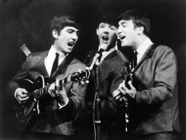 George Harrison, left, Paul McCartney, center and John Lennon, right, three members of the Beatles group during a concert, in London, on Nov. 11, 1963.