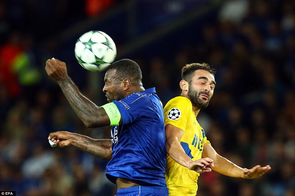 Leicester captain Wes Morgan wins a defensive header under pressure from Adrian Lopez of Porto