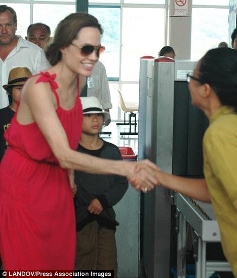 Quando se preparava para embarcar em um avião no Vietnã com seus seis filhos, Angelina moldura fina foi acentuada pelo seu vestido de largas