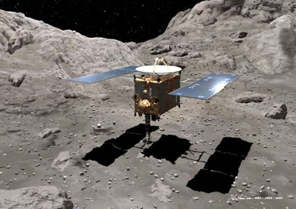 An artist concept showing the HAYABUSA spacecraft collecting rock samples from the surface of asteroid Itokawa.