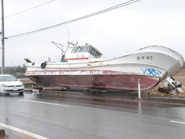 Um ano após o tsunami, um barco continua ao lado de uma estrada de área atingida pela onda gigante no Japão (Foto: Roberto Kovalick/TV Globo )