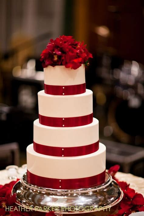 White wedding cake with red ribbon and roses on a silver