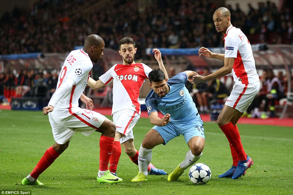 Aguero is crowded out by Fabinho and Djibril Sidibe (left) as he looks to carve a cross down the left-hand side