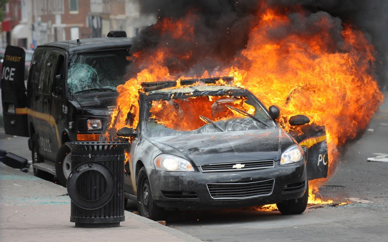 A Maryland Transit Authority patrol car burns at North and Pennsylvania Avenues on Monday, April 27, 2015, in Baltimore. (Jerry Jackson/Baltimore Sun/TNS)