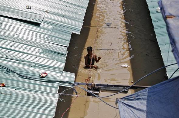 A man wades through a flooded alley at a shopping arcade after heavy monsoon rains caused the rise in waters of Yamuna river in New Delhi, June 20, 2013. REUTERS-Anindito Mukherjee