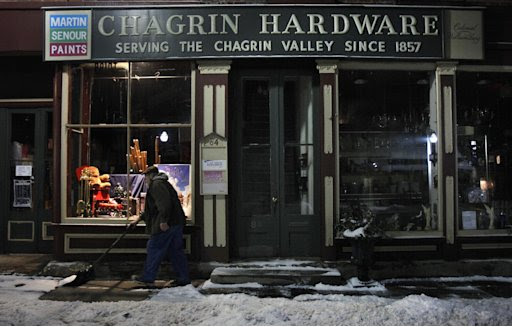 "In the early morning hours of Saturday, Jan. 21, 2012, Rob Schwind shovels the sidewalk in front of the Chagrin Hardware in Chagrin Falls, Ohio. The Shutts family, which has owned the hardware for the last 72 years, was preparing for a community-driven ""Cash Mob"" of the store to happen that day. (AP Photo/Amy Sancetta)"