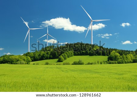 Wind turbine renewable energy source summer landscape with clear blue sky and field in the foreground - stock photo