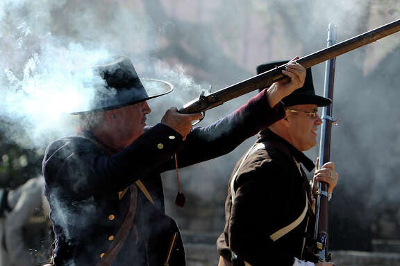 Gun smoke envelopes re-enactor David Martin (left) while he and Jim Wilson charge toward the Mexican Army. Members of the San Antonio Living History Association commemorated the Battle of Bexar and the surrender of Mexican Army Gen. Martin Perfecto de Cos with a reenactment at La Villita on Saturday, Dec. 11. 2010. Martin is president of the Lonestar chapter of the Sons of the Republic of Texas in Montgomery County. About 50 actors gathered to recall the battle of Bexar which occurred from Dec. 5 to 9, 1835 which the Texians defeated the Mexican Army for control of San Antonio. This year marks the 175th anniversary of that battle as well as the battle at the Alamo. Kin Man Hui/kmhui@express-news.net