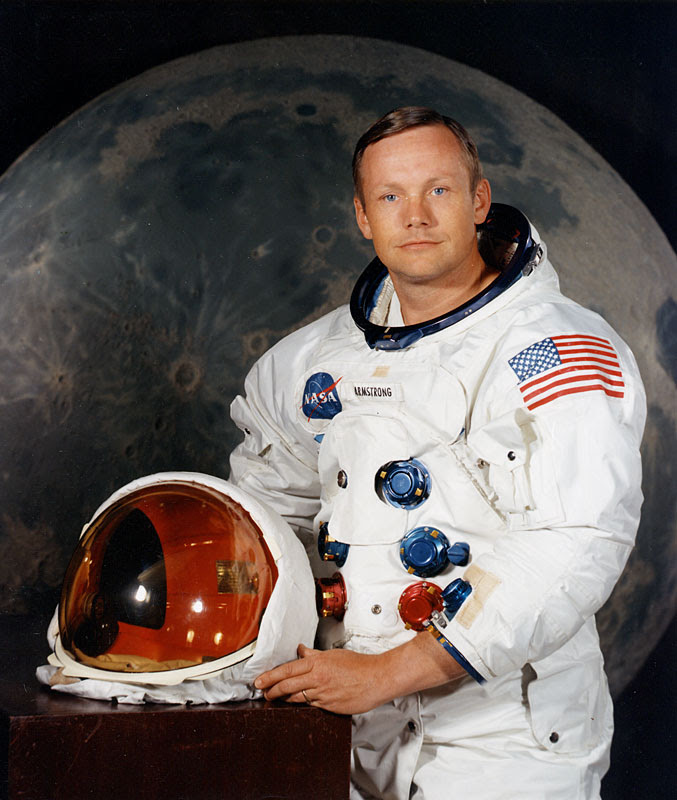 Portrait of Astronaut Neil A. Armstrong, commander of the Apollo 11 Lunar Landing mission in his space suit, with his helmet on the table in front of him. Behind him is a large photograph of the lunar surface.