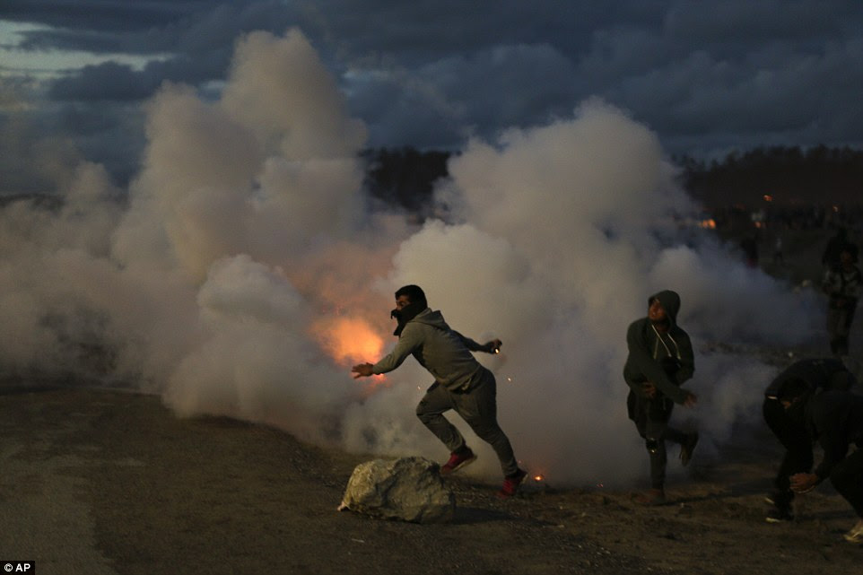 Migrants throw tear gas canisters at French riot police officers during clashes in a makeshift migrant camp known as 'The Jungle'
