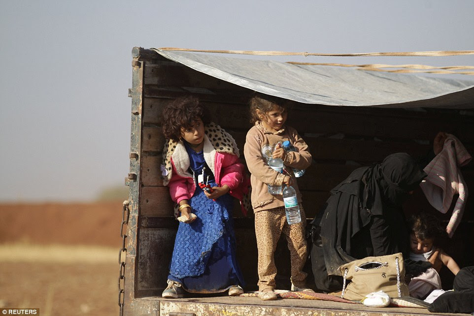 Women and children were pictured riding on the back of a pick-up truck after fleeing the violence in Mosul