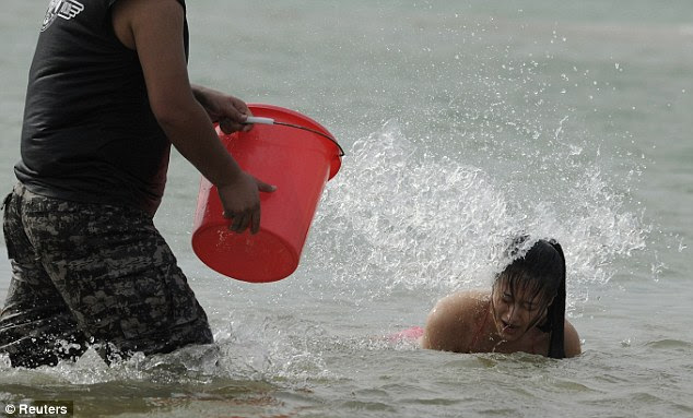 No let up: The woman is then doused in sea water as she comes up for air