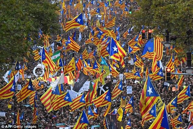 Rajoy argues direct rule is necessary to stop the Catalan government from acting on the results of an outlawed October 1 referendum that Puigdemont said gave him the mandate to declare independence. Pictured: Catalan nationalists wave the region's flag on Saturday