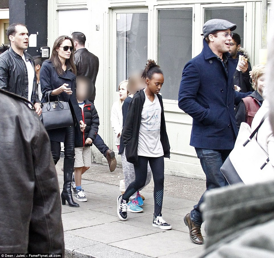 Happy families: With Jolie hanging back, Brad laughed and giggled in the front, with the children walking in sync