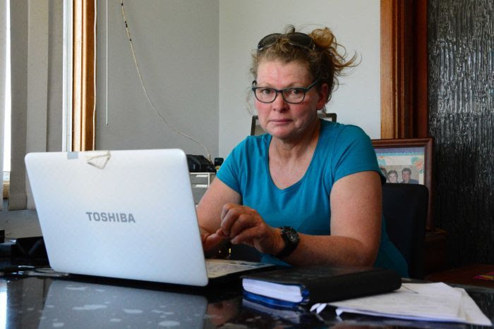 A woman sits indoors wearing a blue shirt and glasses posing for a photo at her laptop.