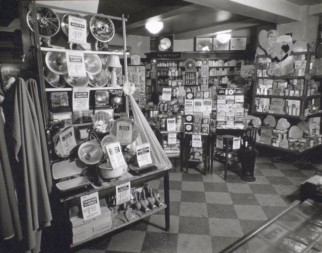 Whelan's Drug Store, 44th Street and Eighth Avenue, Manhattan. Man waits on customer in background, displays of electrical appliances, clocks, and a Valentine's Day display of candy.
