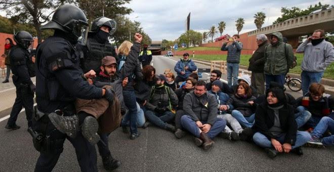 Los Mossos se llevan a una persona en Barcelona durante la huelga en Catalunya. REUTERS/Albert Gea