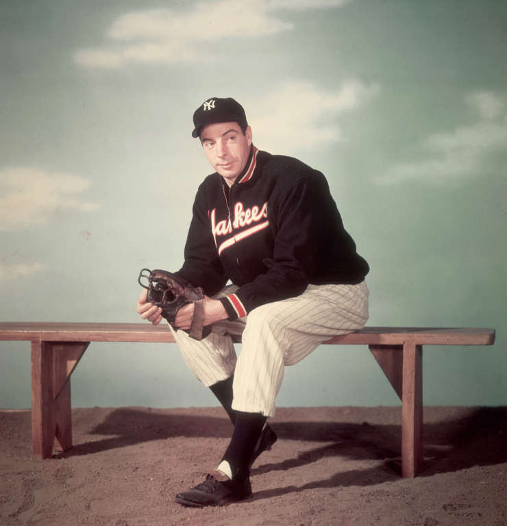 circa 1945:  Studio portrait of American baseball player Joe DiMaggio (1914 - 1999), outfielder for the New York Yankees, sitting on a bench and wearing his uniform in front of a sky backdrop.  (Photo by Hulton Archive/Getty Images)