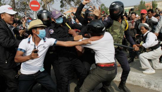 A man is grabbed and beaten by security forces near Phnom Penh's Freedom Park during a 2014 demonstration. Post Staff