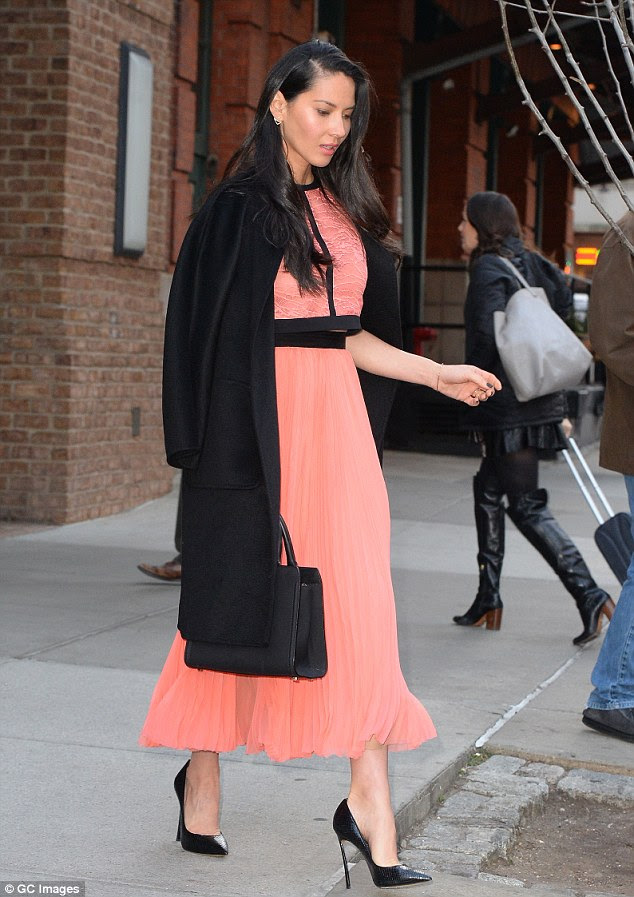Chic accessories: Olivia donned sky-high black heels and draped a coat over her shoulders