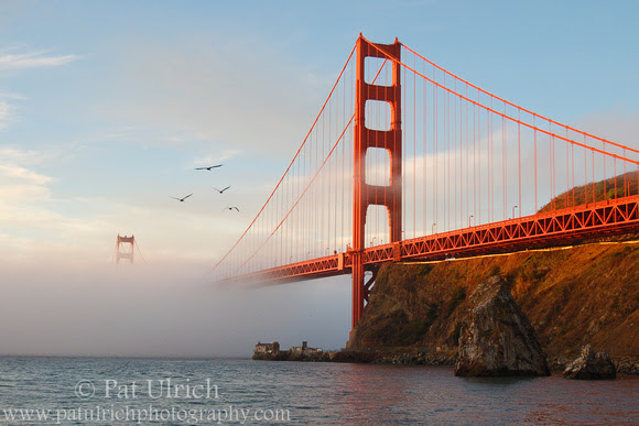 Photograph of the Golden Gate Bridge draped in fog at sunrise