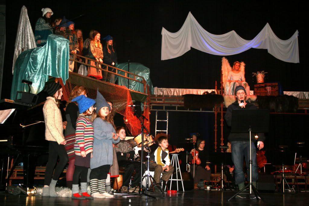 Orkesteret sitter under stillasene og syngende kystnisser popper opp overalt - dyktig vokalist i midten der!
