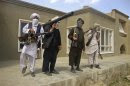 Taliban fighters pose with weapons at an undisclosed location in southern Afghanistan