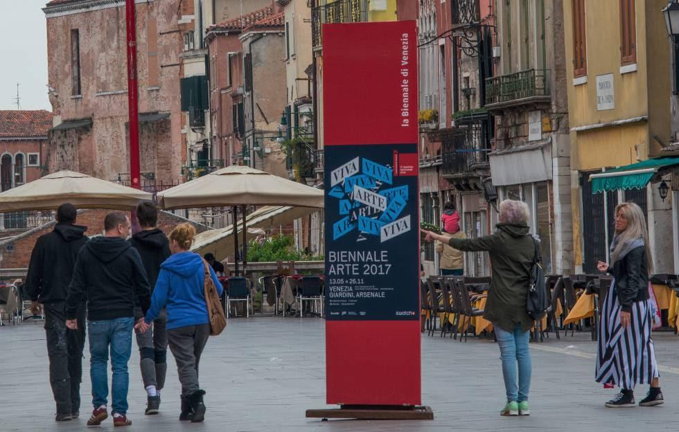 Turistas observan ayer lunes un cartel que anuncia la 57ª Bienal de Venecia.