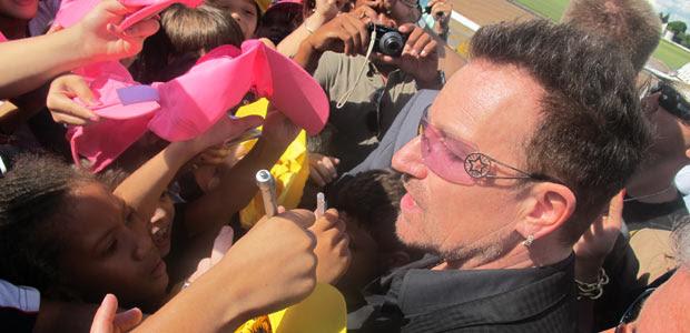 O cantor Bono, do U2, rodeado por fãs na saída do Palácio da Alvorada, após reunião com a presidente Dilma Rousseff (Foto: Débora Santos/G1)