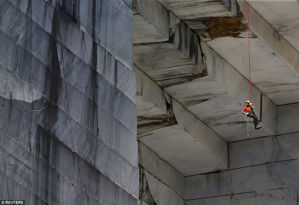 A 'Tecchiaiolo' worker examines marble at the Cervaiole quarry on Monte Altissimo in the Apuan Alps, Tuscany, Italy, on July 18.Michelangelo sculpted most of his statues using stone from the region, which is the country's most marble-rich area