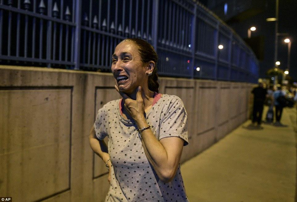 Uma mulher chora fora do aeroporto Ataturk de Istambul, onde três terroristas dispararam no terminal antes de detonar coletes suicidas