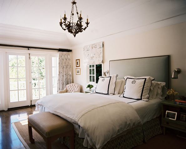 Bedroom - A gray upholstered headboard with white-and-black monogrammed linens