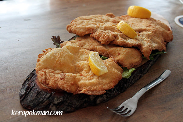 Riesenschnitzel : Giant breaded escalope of pork served on a wooden board