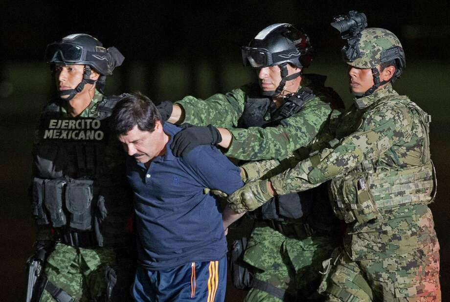 "Mexican army soldiers escort drug lord Joaquin ""El Chapo"" Guzman to a helicopter to be transported to a maximum security prison at Mexicos Attorney Generals hangar, in Mexico City, on Jan. 8. Photo: Eduardo Verdugo /Associated Press / AP"