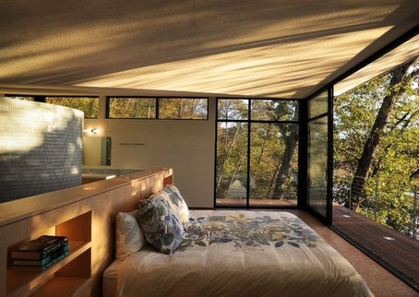 Contemporary bedroom with floor-to-ceiling glass walls and a narrow balcony