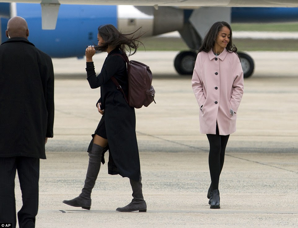Sasha (left) and Malia Obama walk towards Air Force One upon the arrival to Andrews Air Force Base, before their departure