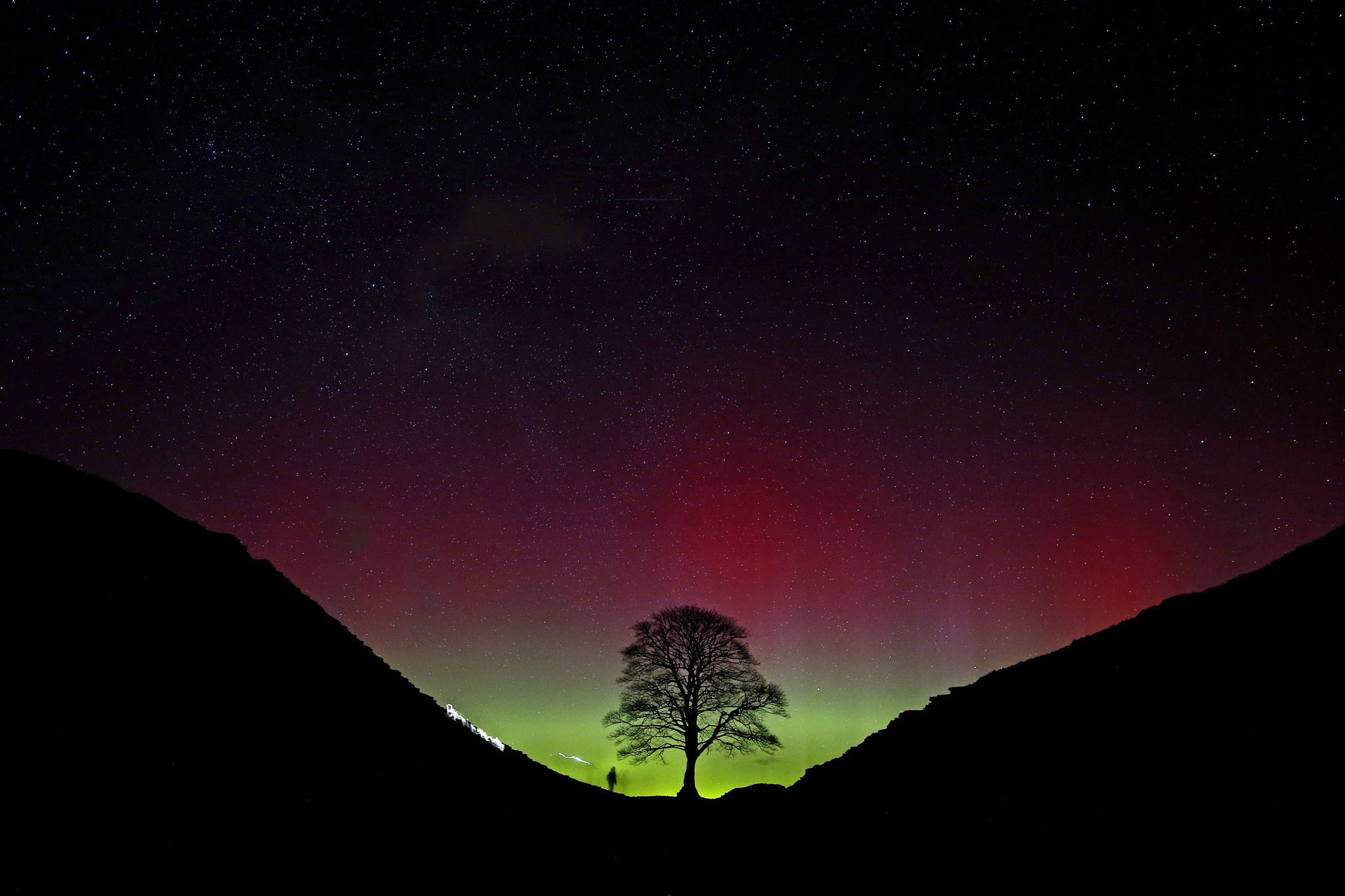 Spring weather Mar 7th 2016...The Northern Lights, or Aurora Borealis, shine over the Sycamore Gap at Hadrian's Wall in Northumberland. PRESS ASSOCIATION Photo. Picture date: Sunday March 6, 2016. The ethereal spectacle is caused by charged solar particles interacting with the Earth's magnetic field and is usually only visible in the far north of Scotland. See PA story WEATHER Aurora. Photo credit should read: Owen Humphreys/PA Wire