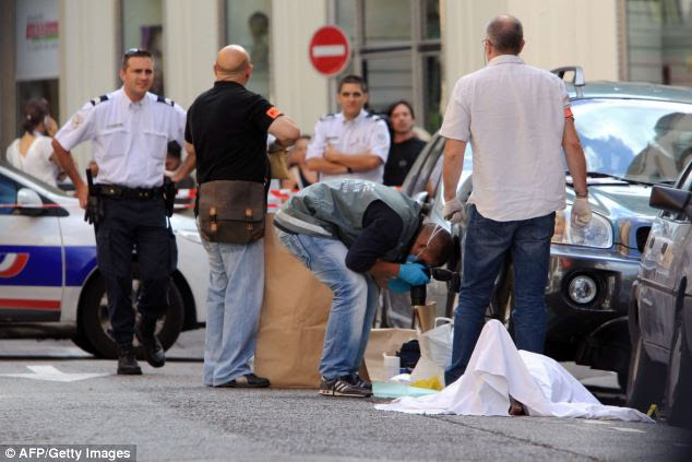 Forensic experts and police work at the scene where an armed robber was shot dead